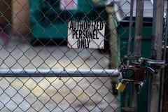 Gemachtigde personeelsledenteken op een omheining van de kettingsverbinding met dumpsters royalty-vrije stock fotografie