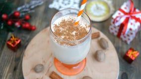 Gemada quente picante da bebida do Natal tradicional caseiro da preparação com noz-moscada à terra, canela em um vidro, filme
