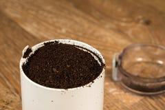 Gemahlener Kaffee im Schleifer auf Holztisch Stockbilder