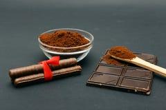 Gemahlener Kaffee und Schokolade auf dem schwarzen Hintergrund und dem frischen angehäuften Kaffee auf hölzernem Löffel Stockbilder