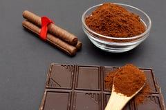 Gemahlener Kaffee und Schokolade auf dem schwarzen Hintergrund und dem frischen angehäuften Kaffee auf hölzernem Löffel Stockfoto