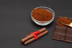 Gemahlener Kaffee und Schokolade auf dem schwarzen Hintergrund und dem frischen angehäuften Kaffee auf hölzernem Löffel Stockfotos