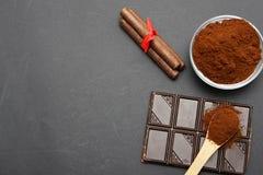 Gemahlener Kaffee und Schokolade auf dem schwarzen Hintergrund und dem frischen angehäuften Kaffee auf hölzernem Löffel Lizenzfreies Stockfoto