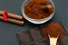 Gemahlener Kaffee und Schokolade auf dem schwarzen Hintergrund und dem frischen angehäuften Kaffee auf hölzernem Löffel Lizenzfreie Stockbilder