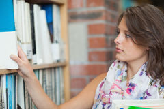 Gemale student selecting book from the shelf in library Stock Photo