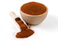 Gemalen of gemalen paprika of Spaanse peper in houten kom en lepel die op witte achtergrond wordt ge?soleerd Kruiden en voedselin stock fotografie