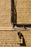Gemalte Backsteinmauer mit einem Bündel elektrischer Verdrahtung Stockfoto