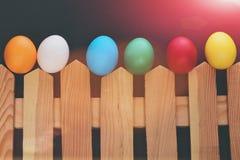 Gemalte bunte Eier Ostern auf Bretterzaun auf schwarzem Hintergrund Lizenzfreies Stockfoto