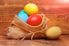 Gemalte bunte Eier Ostern im Leinwandsack auf hölzernem Hintergrund Stockfotografie