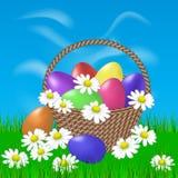 Gemalte Eier in einem Korb und in den Gänseblümchen Stockfotografie