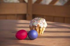 Gemalte Eier und Kuchen auf einem Holztisch stockfotografie