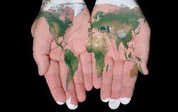Gemalte Karte der Welt in unseren Händen Stockfotografie