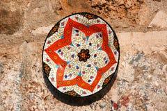 Gemalte keramische Platte mit hellem orientalischem Muster auf einer Steinwand Stockbilder