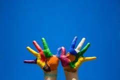 Gemalte Kinderhände auf blauer Himmel backgrobnd lizenzfreie stockfotos