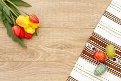 Gemalte Ostereier auf Tuch mit Verzierung, Tulpen auf hölzerner Boa Stockfotos
