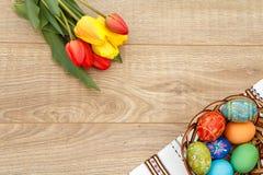 Gemalte Ostereier auf Tuch mit Verzierung, Tulpen auf hölzerner Boa Lizenzfreies Stockbild