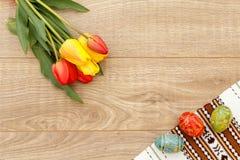 Gemalte Ostereier auf Tuch mit Verzierung, Tulpen auf hölzerner Boa Stockfotografie