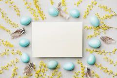 Gemalte Ostereier, Mimosenblume und Papierkarte auf Weinlese entsteinen Draufsicht des Hintergrundes in der Ebenenlageart Leerer  Stockfoto