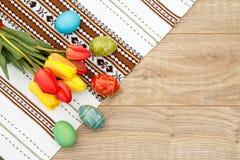 Gemalte Ostereier, Tulpen und Tuch mit Verzierung auf hölzernem BO Lizenzfreies Stockbild