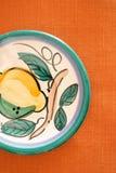 Gemalte Platte auf orange Tabellen-Tuch Lizenzfreies Stockbild