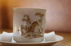 Gemalte Porzellanteeschale mit Muster des Landschaftshauses, mit Würfeln des Zuckers Stockfotografie
