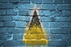 Gemalte Staatsflagge der St. Lucia auf einer Backsteinmauer Lizenzfreie Stockfotografie