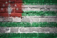 Gemalte Staatsflagge von Abchasien auf einer Backsteinmauer Stockfotografie