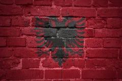 Gemalte Staatsflagge von Albanien auf einer Backsteinmauer Lizenzfreie Stockbilder