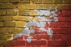 Gemalte Staatsflagge von Bhutan auf einer Backsteinmauer Lizenzfreies Stockfoto