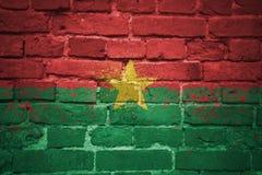 Gemalte Staatsflagge von Burkina Faso auf einer Backsteinmauer Lizenzfreie Stockfotos