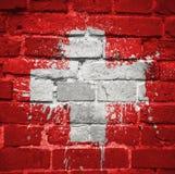 Gemalte Staatsflagge von der Schweiz auf einer Backsteinmauer Stockfotos