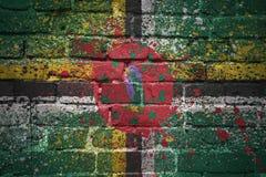 Gemalte Staatsflagge von Dominica auf einer Backsteinmauer Stockfotografie