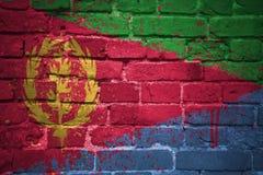 Gemalte Staatsflagge von Eritrea auf einer Backsteinmauer Stockfotos
