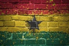 Gemalte Staatsflagge von Ghana auf einer Backsteinmauer Lizenzfreie Stockbilder
