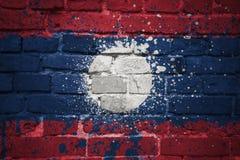 Gemalte Staatsflagge von Laos auf einer Backsteinmauer Stockbild