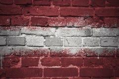 Gemalte Staatsflagge von Lettland auf einer Backsteinmauer Lizenzfreies Stockbild