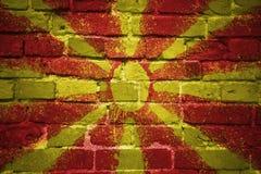 Gemalte Staatsflagge von Macedonia auf einer Backsteinmauer Lizenzfreie Stockbilder
