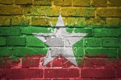Gemalte Staatsflagge von Myanmar auf einer Backsteinmauer Stockfotografie