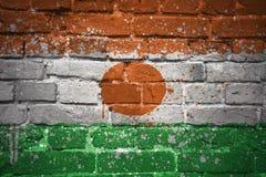 Gemalte Staatsflagge von Niger auf einer Backsteinmauer Lizenzfreies Stockbild