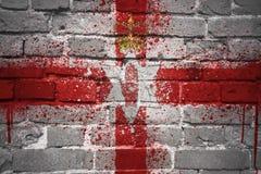 Gemalte Staatsflagge von Nordirland auf einer Backsteinmauer Stockfoto