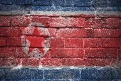 Gemalte Staatsflagge von Nordkorea auf einer Backsteinmauer Stockfoto