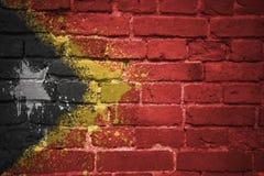 Gemalte Staatsflagge von Osttimor auf einer Backsteinmauer Stockfotos
