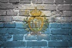 Gemalte Staatsflagge von San Marino auf einer Backsteinmauer Lizenzfreies Stockbild