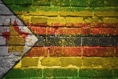 Gemalte Staatsflagge von Simbabwe auf einer Backsteinmauer Lizenzfreie Stockbilder