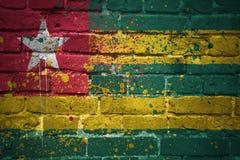 Gemalte Staatsflagge von Togo auf einer Backsteinmauer Stockbild