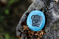 Gemalter blauer Felsen mit glänzendem grauem Elefanten stockfotografie
