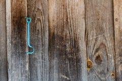 Gemalter blauer Schließhaken, der an der alten braunen Holztür hängt stockbilder