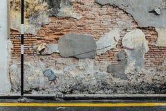 Gemalter Junge, der Drachen mit wirklichem Hut auf der roten Tür mit Wand des roten Backsteins von der Straße von George Town spi Lizenzfreie Stockfotografie
