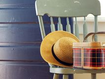 Gemalter Stuhl mit Strohhut- und Weinleseplaidpicknickkorb Stockfoto