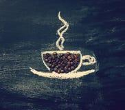 Gemalter Tasse Kaffee mit natürlichen Kaffeebohnen auf einer Tafel Lizenzfreie Stockbilder